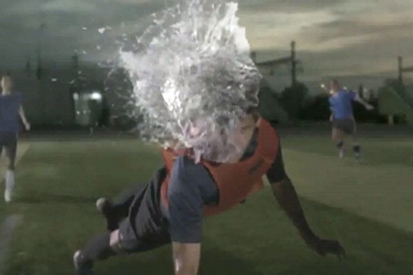 Futbolista dando cabezazo a balón de agua.