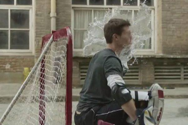 Jugador de hockey recibiendo impacto de disco de agua.