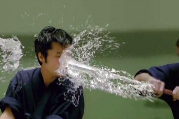 Luchador recibiendo el impacto de una katana que se convierte en agua.